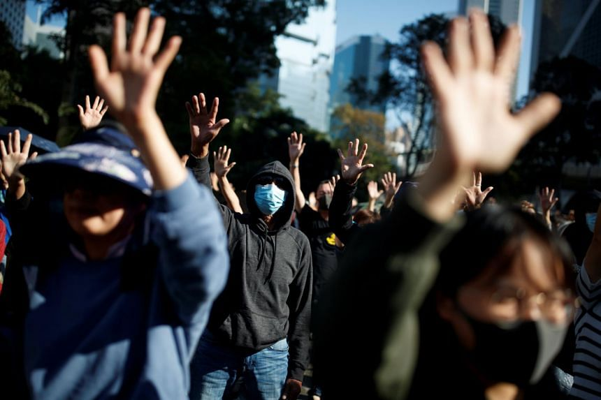 People raise their hands as they sing the protest anthem Glory To Hong Kong during a protest in the Central district of Hong Kong, on Nov 30, 2019.