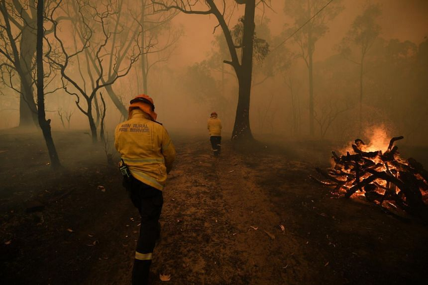 New South Wales Rural Fire Service and Fire and Rescue NSW crews work to protect a property in Kulnura as the Three Mile fire approaches Mangrove Mountain, Australia, on Dec 6, 2019.
