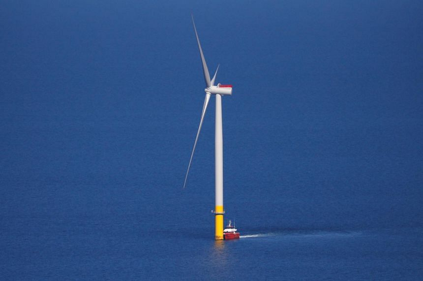 In a photo taken on Sept 5, 2018, a support vessel is seen next to a wind turbine at the Walney Extension offshore wind farm operated by Orsted off the coast of Blackpool, Britain.