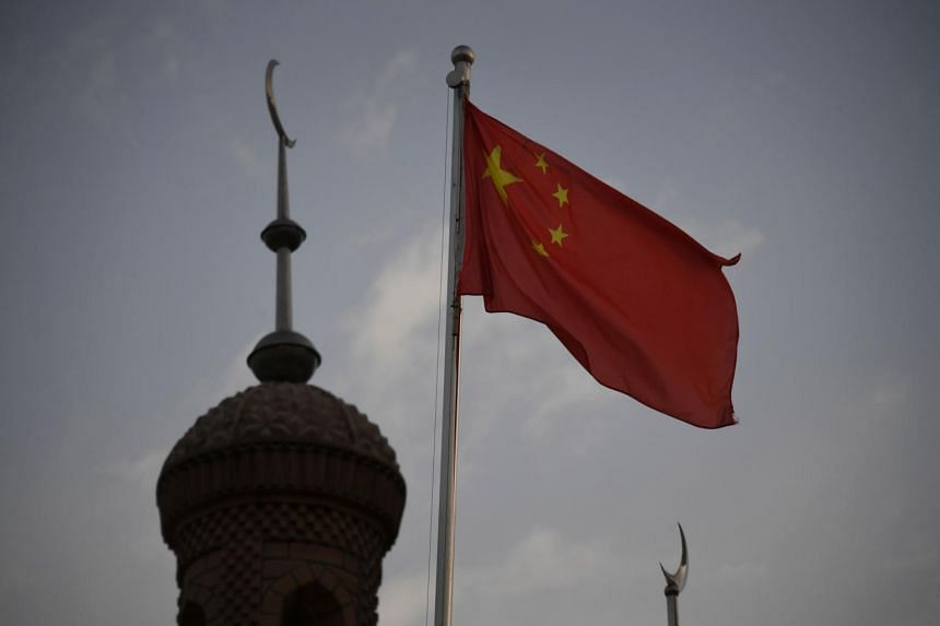 A photo taken on June 4, 2019, shows the Chinese flag flying over the Juma mosque in the restored old city area of Kashgar in China's western Xinjiang region.