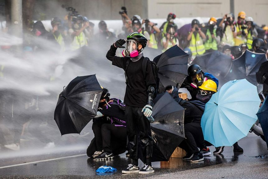 In a photo taken on Sept 15, 2019, pro-democracy protesters react as police fire water cannons outside the government headquarters in Hong Kong.