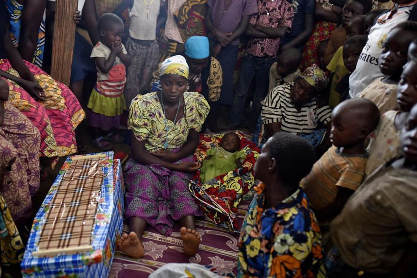 In a photo from June 25, 2019, Congolese victims of ethnic violence prepare the burial of a child suspected to have died of measles in Bunia, Ituri province in the Democratic Republic of Congo.