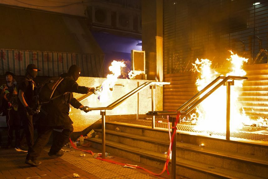 In a photo from Dec 1, 2019, pro-democracy protesters set fire at an entrance gate of Whampoa MTR station in Hong Kong.