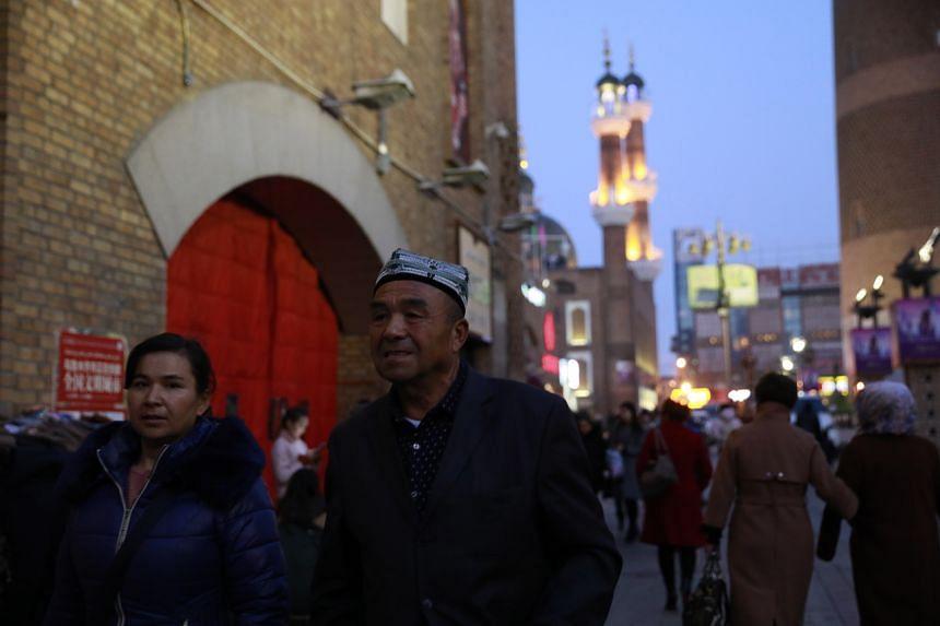 In a photo taken on Nov 18, 2017, ethnic Uighur minority people walk in Dabazha or Grand Bazaar in Urumqi city.