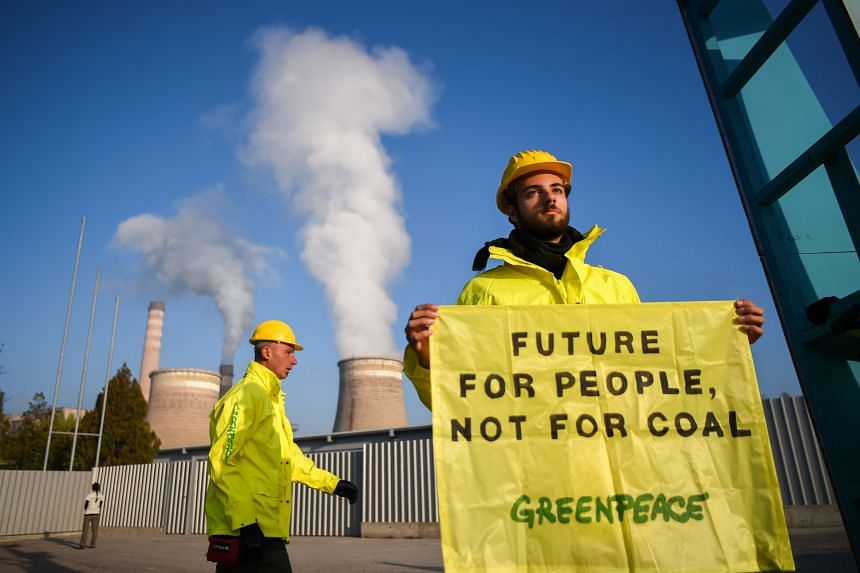 In a photo taken on Oct 13, 2019, a Greenpeace activist holds a banner in front of the Republika Power Plant, the oldest functioning coal plant in Europe, during a protest calling to phase out coal in the town of Pernik, in Bulgaria.