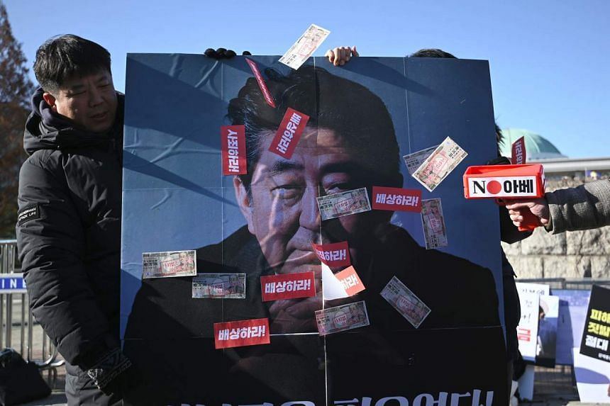 South Korean protesters spray fake money on a picture of Japan's Prime Minister Shinzo Abe during an anti-Japan rally denouncing a Bill on Japan's wartime forced labour in Seoul on Dec 5, 2019.