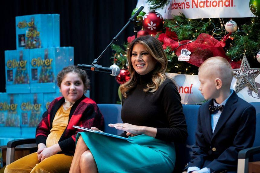 Melania Trump reads as patients Sammie Burley (left) and Declan McCahan listen.