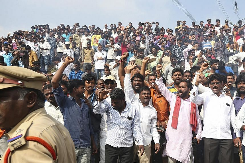 Police (above) yesterday at the site where officers killed four detained rape and murder suspects who were trying to escape in Shadnagar, near the Indian city of Hyderabad. A crowd (left) near the scene of the killings shouting slogans in support of