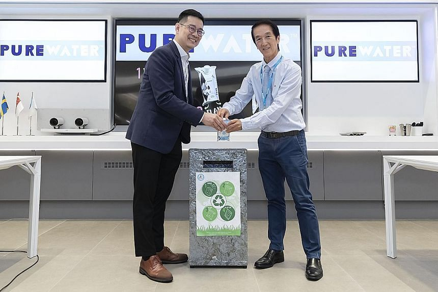 Polar Water managing director Chew Thye Chuan (right) and Mr David Tan, key account director of Tetra Pak Malaysia, Singapore, the Philippines and Indonesia, recycling a used Purewater carton. PHOTO: POLAR WATER DISTRIBUTOR