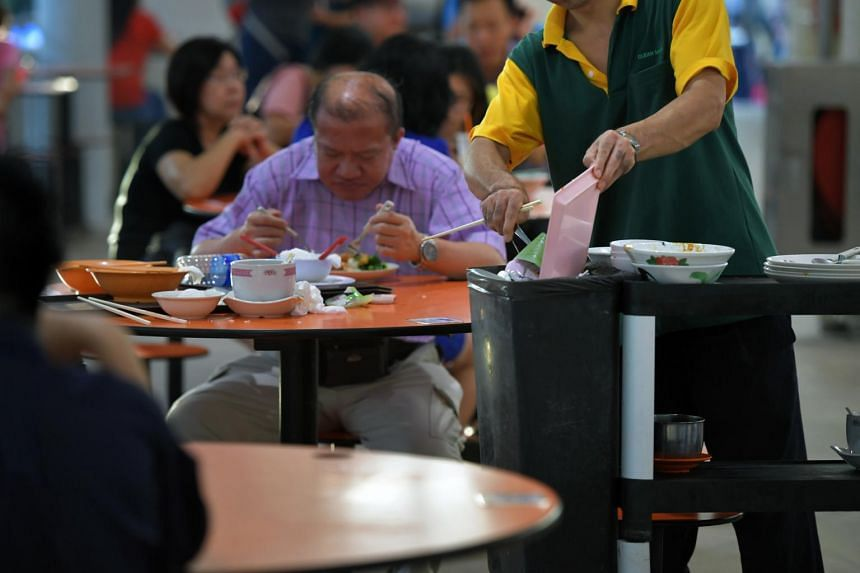 A cleaner clearing the dishes on a table at the Bedok Interchange Hawker Centre.