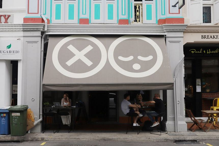 The all-day bar and restaurant is fronted by a taupe awning with two emojis (above).
