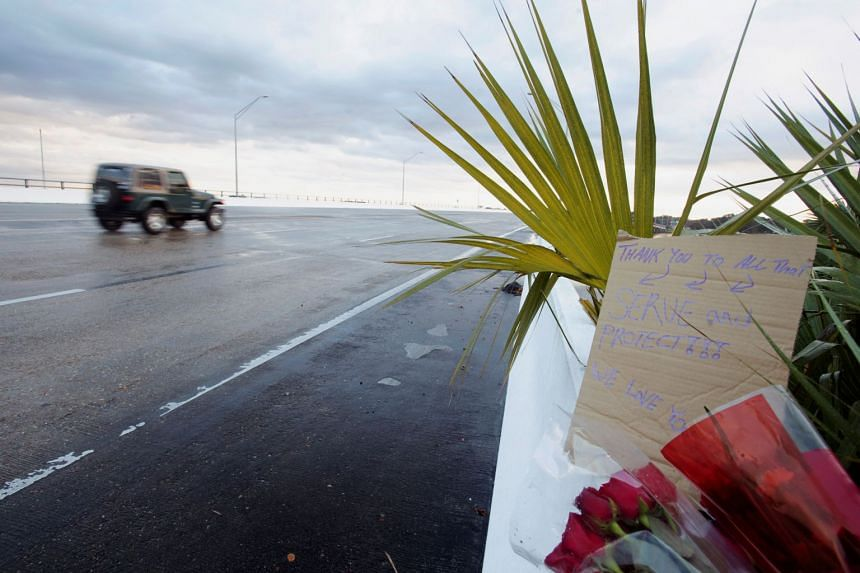 Flowers and a message are left on the entrance bridge at Naval Air Station Pensacola.