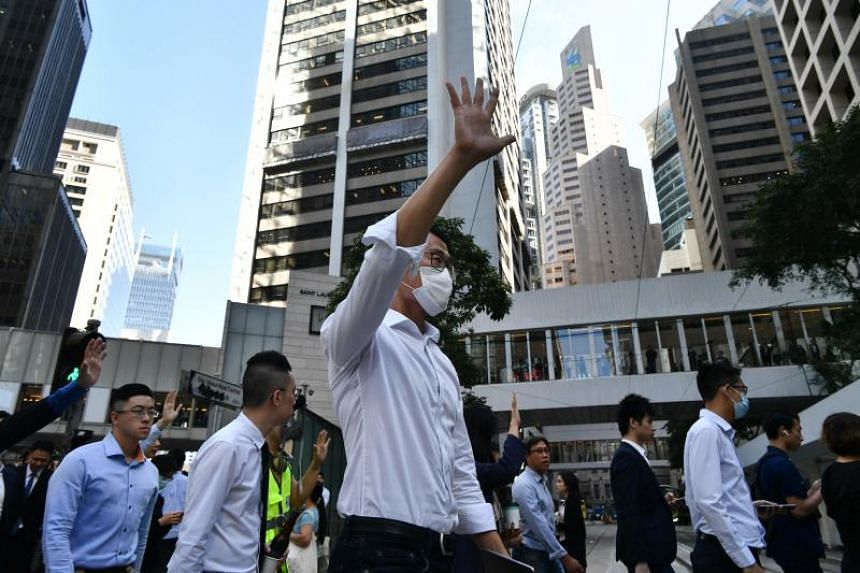 In a photo from Nov 25, 2019, office workers shout slogans during a lunchtime protest in the Central district in Hong Kong.