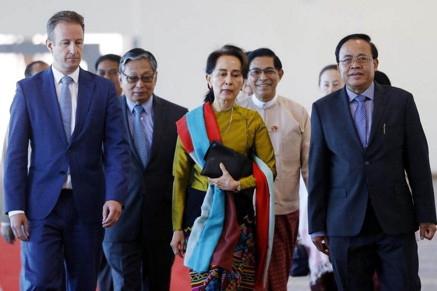 Myanmar's State Counsellor Aung San Suu Kyi (centre) and Wouter Jurgens (left), Netherlands ambassador to Myanmar, speak as Suu Kyi prepares to leave from Naypyitaw International Airport in on Dec 8, 2019.