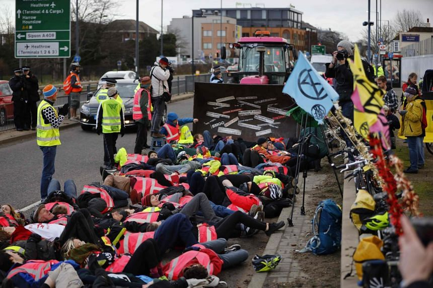 """Extinction Rebellion activists perform a """"bulldozer lie-in"""" as they demonstrate against the building of a third runway at Heathrow Airport in London on Dec 8, 2019."""