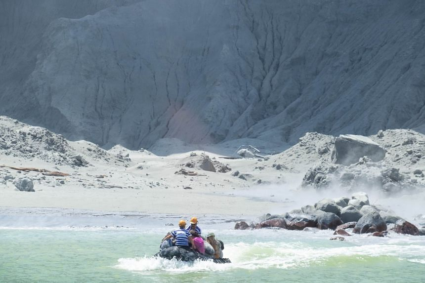 Tour guides evacuate tourists on a boat shortly after the volcano eruption on White Island.