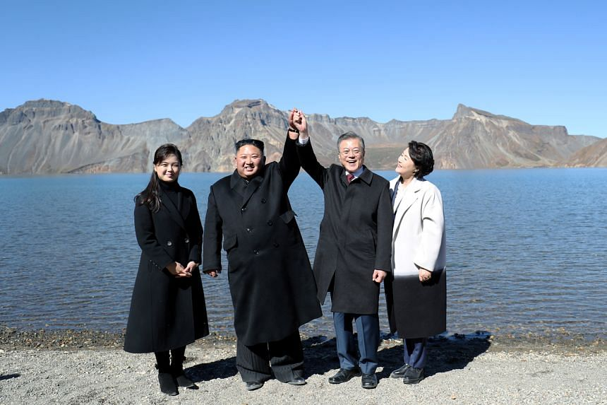 In a photo taken on Sept 20, South Korean President Moon Jae-in, first lady Kim Jung-sook, North Korean leader Kim Jong Un and his wife Ri Sol Ju pose for photographs beside the Heaven Lake of Mt. Paektu, North Korea.