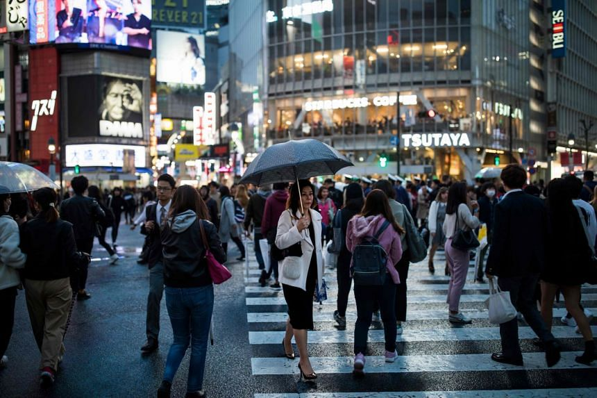 Commuters make their way over the Shibuya crossing in central Tokyo, on Oct 29, 2019.