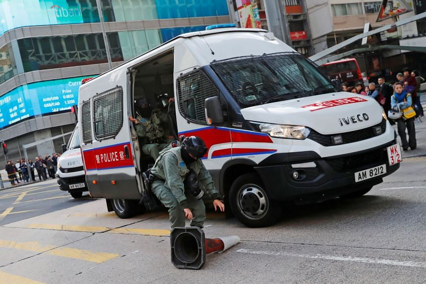 A riot police officer removes a traffic cone thrown by a protester to block the traffic, outside Mong Kok station in Hong Kong, on Dec 9, 2019.