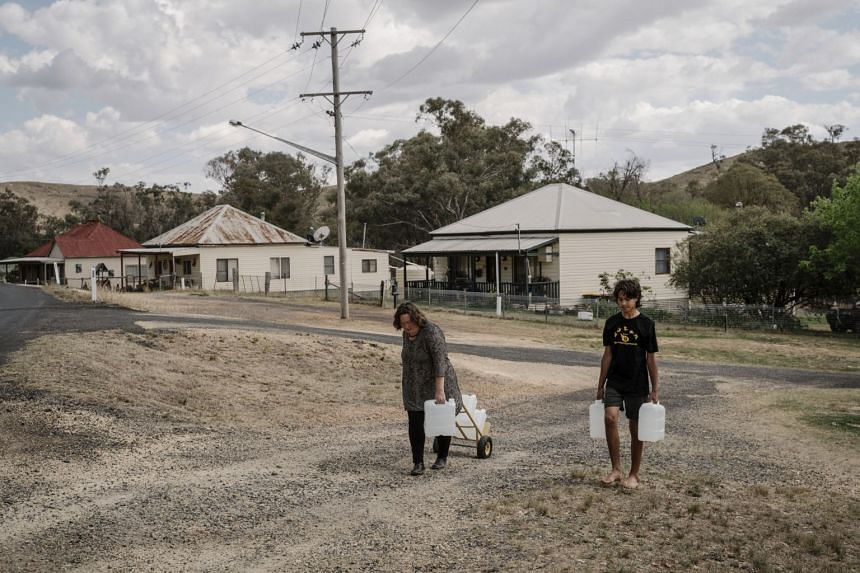 Fleur Magick Dennis and her son, James, carry drinking water home from the town hall in Euchareena, New South Wales, on Oct 10, 2019.