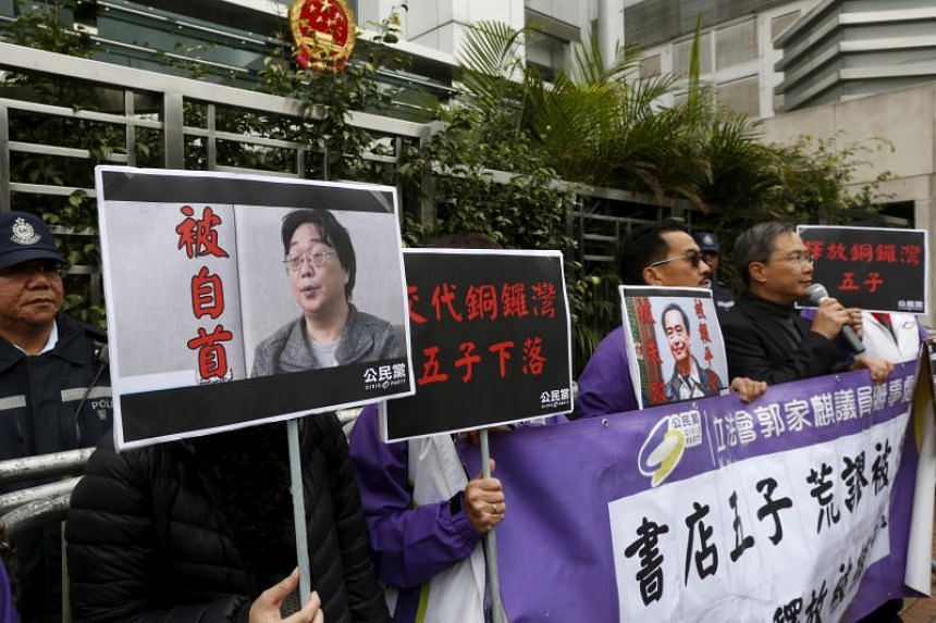 A photo taken on Jan 19, 2016, shows protesters, holding portraits of missing booksellers, outside the Chinese Liaison Office in Hong Kong.