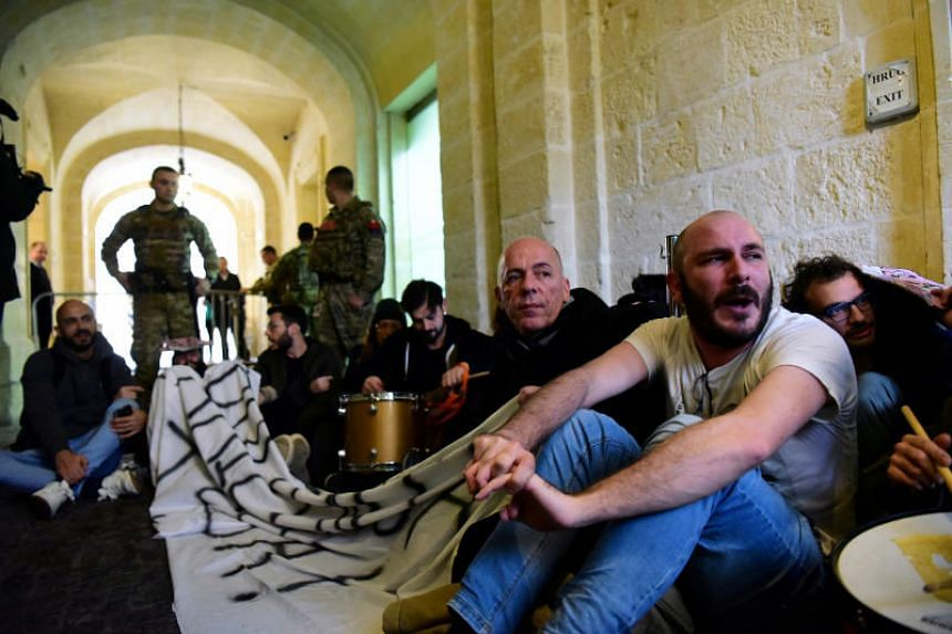 Activists sit after they barged into the building of Malta's Prime Minister Joseph Muscat's office, demanding his resignation in the wake of developments in case of the 2017 murder of journalist Daphne Caruana Galizia, on Dec 9, 2019.