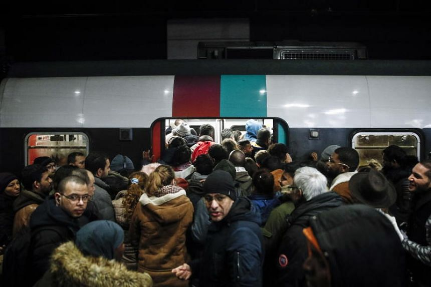 Commuters trying to enter a packed train during a general strike action at Gare Du Nord train station in Paris on Dec 9, 2019. Unions representing railway and transport workers have called for a general strike to protest against French government's r