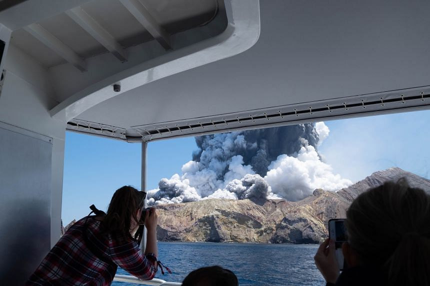 Tourists on a boat look at the eruption of the volcano on White Island, New Zealand, on Dec 9, 2019.