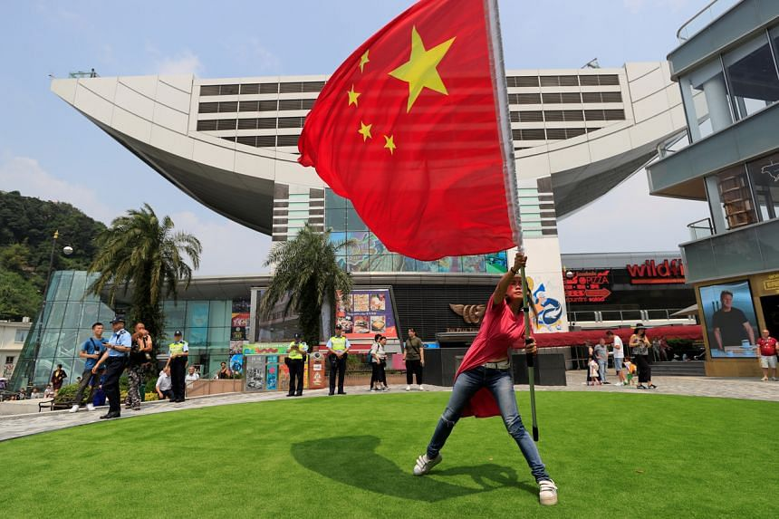 A pro-China supporter holds a Chinese national flag during a rally at Victoria Peak in Hong Kong, on Sept 29, 2019.