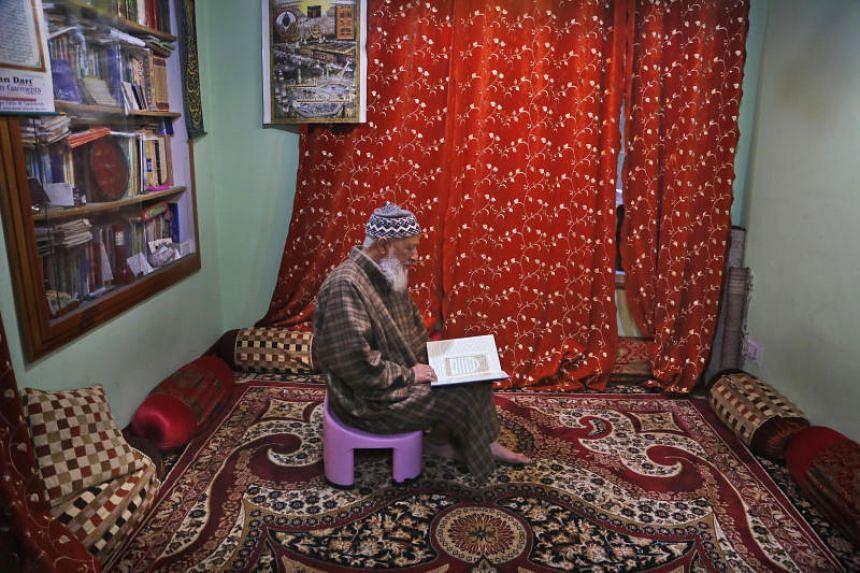 Mohammed Yasin Bangi reads the Quran inside his home in Srinagar, Kashmir, on Nov 19, 2019.