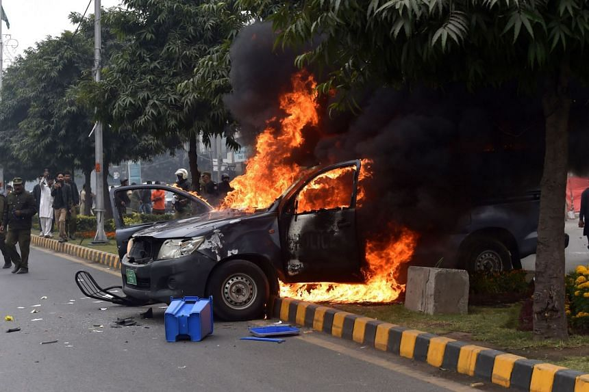 A police vehicle is set ablaze during a clash between lawyers and doctors outside the Punjab Institute of Cardiology.