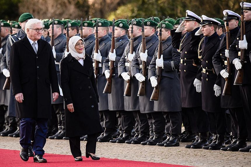 Left: President Halimah inspecting a military guard of honour contingent with German President Frank-Walter Steinmeier during a ceremonial welcome at the Schloss Bellevue in the German capital yesterday.