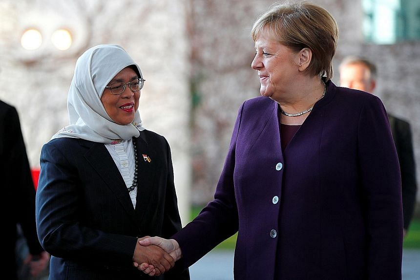 President Halimah Yacob being welcomed by German Chancellor Angela Merkel at the Federal Chancellery in Berlin yesterday.