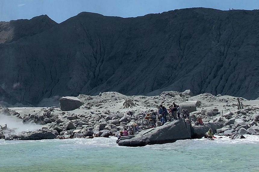 """Tourists waiting to leave White Island in New Zealand on Monday, following the eruption of the volcano. Three weeks before it erupted, the volcano showed signs of """"moderate and heightened volcanic unrest"""". PHOTO: ASSOCIATED PRESS"""