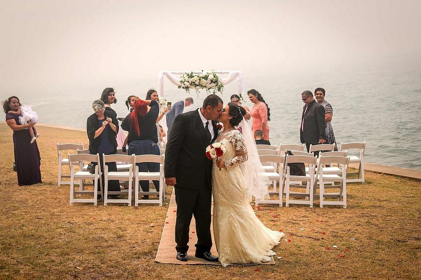 Haze or not, this couple went ahead with their marriage on the foreshore of Sydney Harbour yesterday, even as alarm bells were going off in the city with dense smoke from fierce bush fires entering offices, homes and university campuses, triggering f