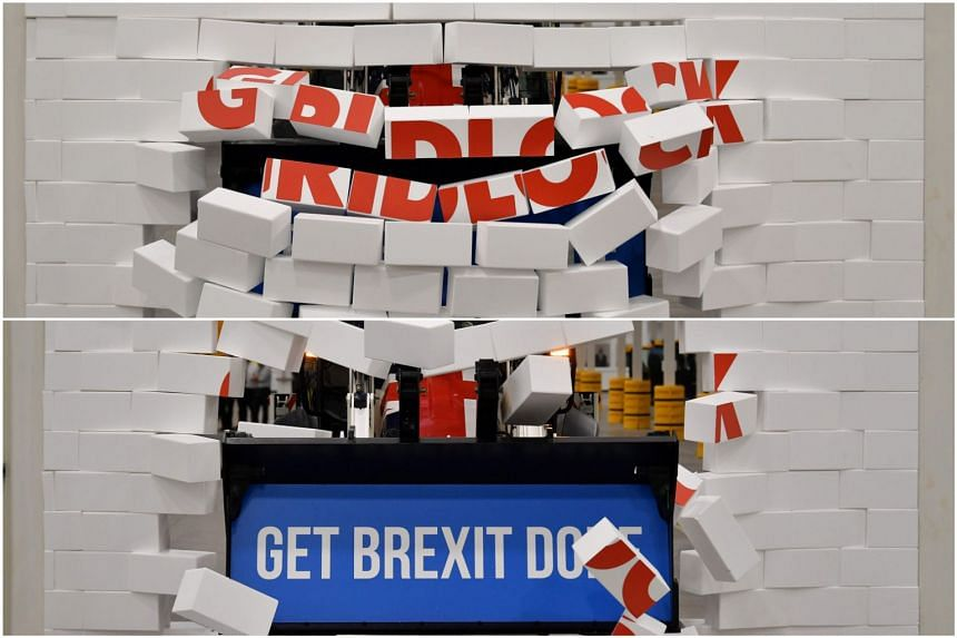 """Britain's PM Boris Johnson drives a Union flag-themed JCB, with the words """"Get Brexit Done"""" inside the digger bucket, through a fake wall emblazoned with the word """"GRIDLOCK"""", on Dec 10, 2019."""