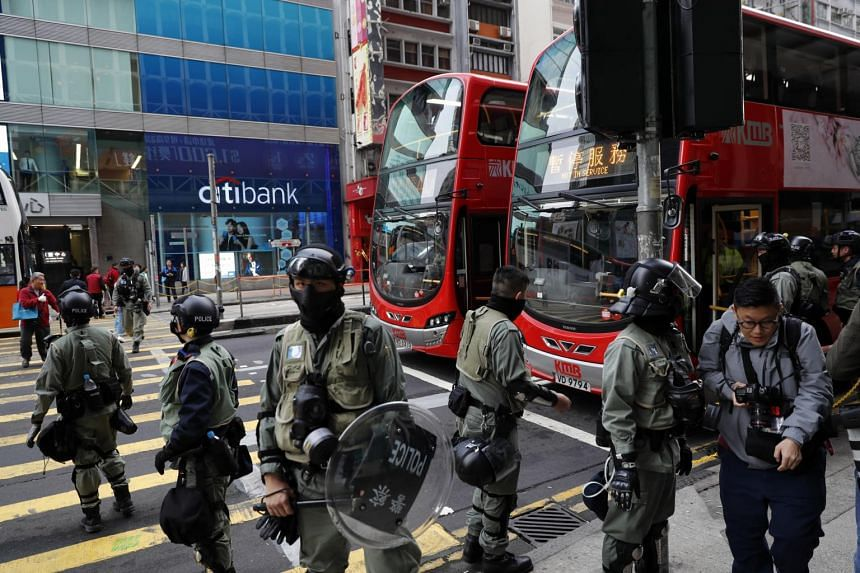 Police standing guard in front of a bus stop in Hong Kong on Dec 9, 2019.