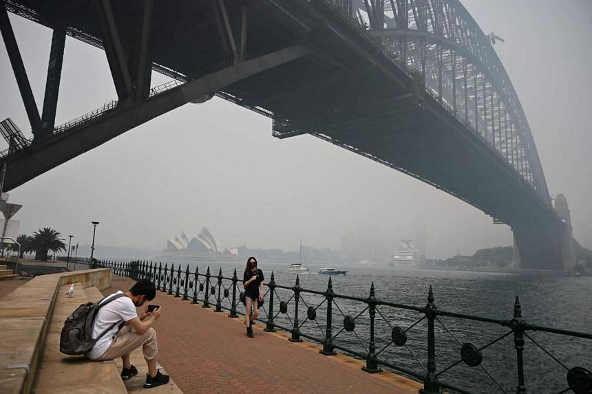 Tourists wearing masks take photos under the Harbour Bridge enveloped in haze caused by nearby bush fires, in Sydney on Dec 10, 2019.