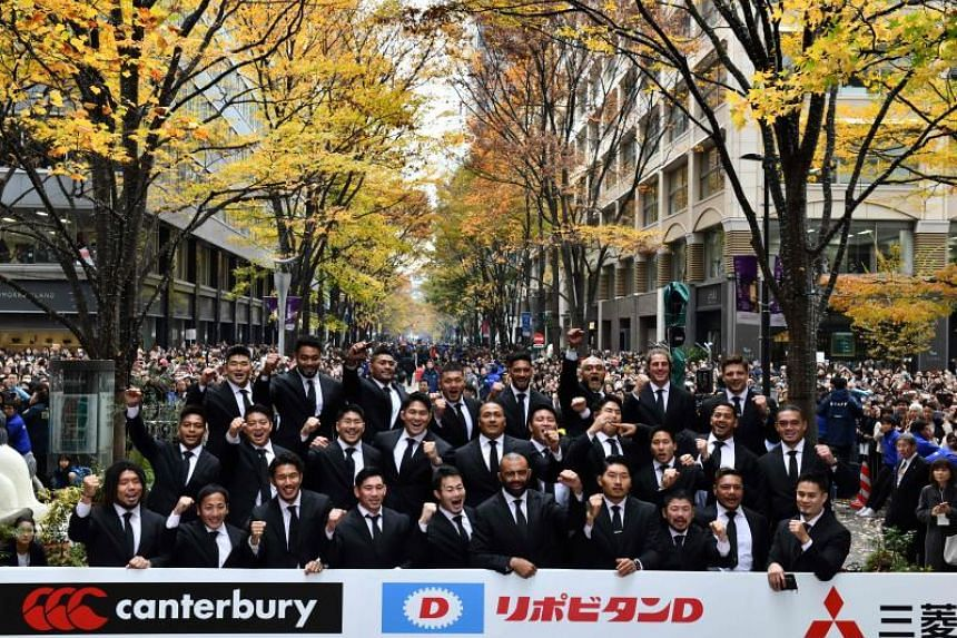 Japan's Brave Blossoms captain and flanker Michael Leitch (front centre) and his teammates pose for a photo during a parade following their Japan 2019 Rugby World Cup campaign, in Tokyo, on Dec 11, 2019.