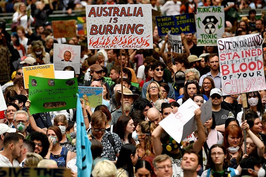 Protesters at a rally in Sydney yesterday, demanding urgent climate action from Australia's government as bush-fire smoke continued to choke the city, causing health problems to spike.