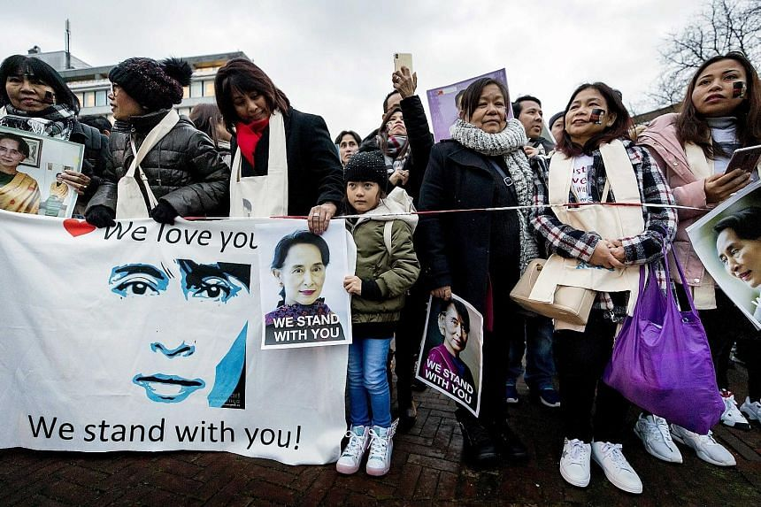 Demonstrators supporting Myanmar standing in front of the Peace Palace in The Hague yesterday. Myanmar's de facto leader Aung San Suu Kyi appeared before the International Court of Justice yesterday to defend her country against accusations of genoci