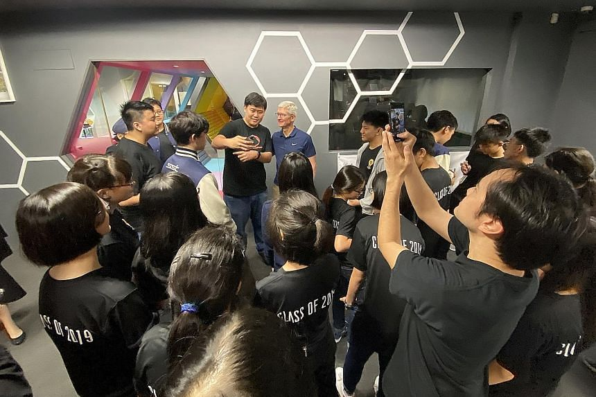 Apple chief executive Tim Cook meeting students at the School of Science and Technology, Singapore yesterday. It is the only school in Singapore to run a compulsory coding programme for all Grade 9 students using Swift, Apple's programming language.