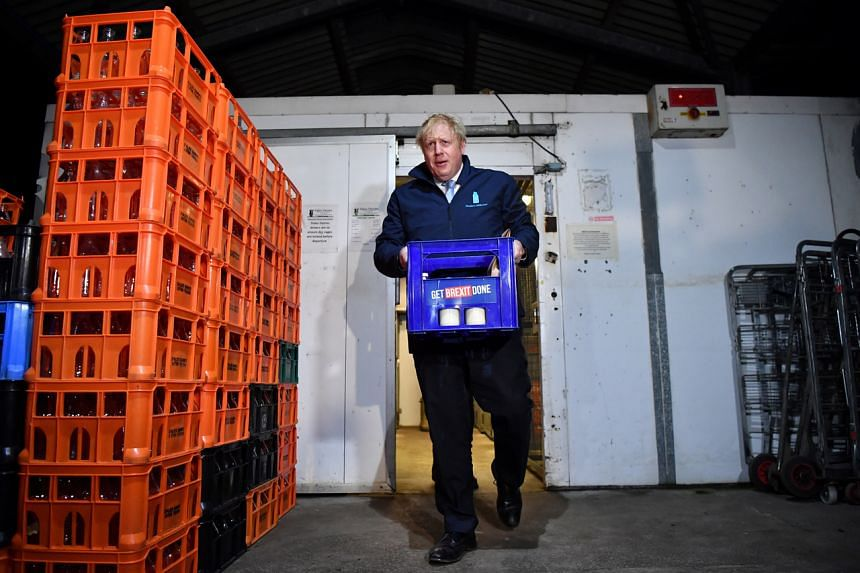 British Prime Minister Boris Johnson emerges from an oversized refrigerator with a crate of milk in Leeds, Yorkshire, on Dec 11, 2019.