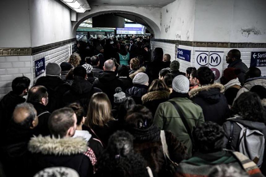 Commuters queue to access a subway platform in Paris on Dec 12, during a strike by public transport operators SNCF and RATP employees.