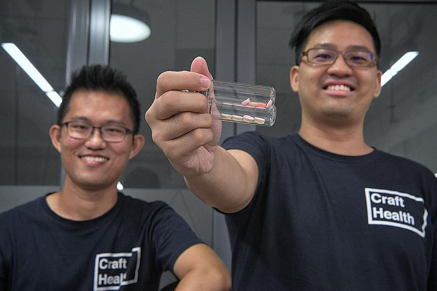 Dr Lim Seng Han (far left) and Dr Goh Wei Jiang of Craft Health with pills made using technology they discovered, which can 3D-print tablets that combine multiple active ingredients in one pill, with different dosages and release times.