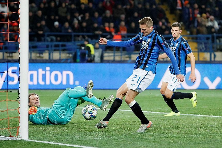 Atalanta defender Timothy Castagne scoring his team's first goal in the 3-0 win over Shakhtar Donetsk on Wednesday night. The Italian Serie A side advanced despite losing their first three group matches. Below: Atletico Madrid forward Joao Felix cele