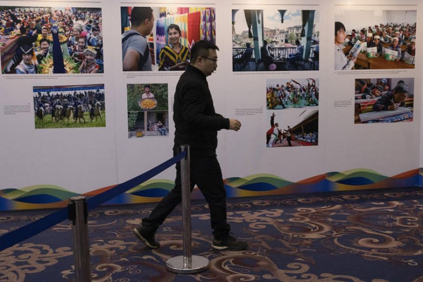 A man walks past a display of photos from Xinjiang during a forum on human rights in Beijing on Dec 11, 2019.