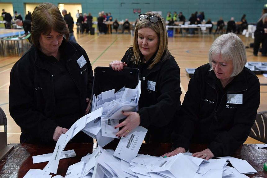 Ballot boxes being emptied before sorting begins at a count centre in Bishopbriggs, north of Glasgow, Scotland.