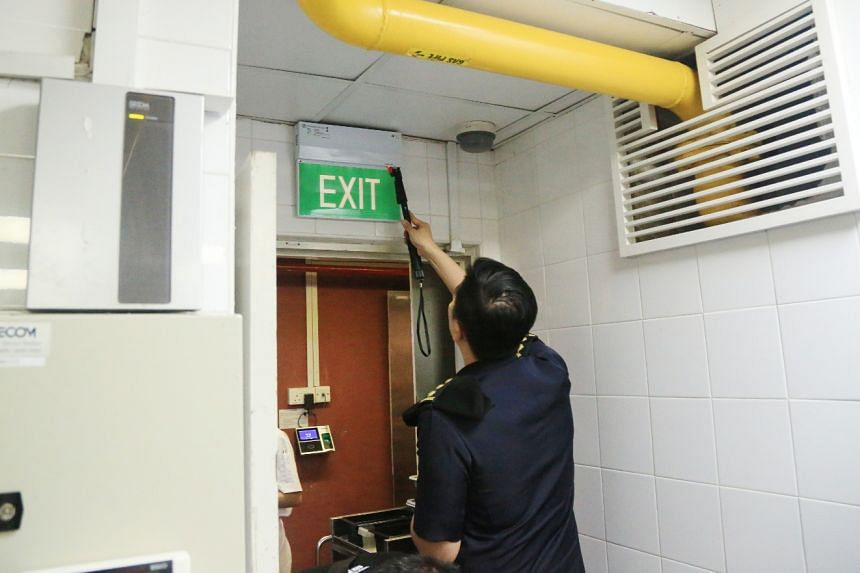 Officers inspecting the serviceability of an exit sign. In the event of an emergency, these signs must be lit to guide people towards the nearest exit.
