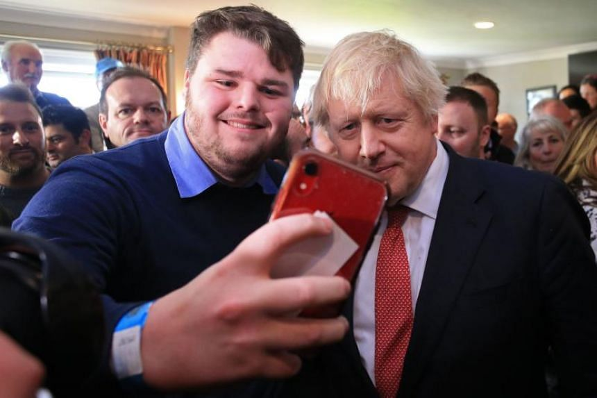 British Prime Minister Boris Johnson takes a selfie photo with a supporter during a visit to Sedgefield, in north-east England, on Dec 14, 2019.